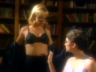 Two very sensual librarians in stockings and garters kiss and caress