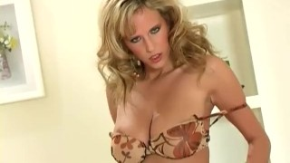 Big boobed blonde stripping and teasing in nude stockings and panties