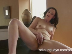 Emily Marshall gets randy in the kitchen and rubs her mature pussy.
