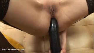 Brunette in stockings gaping her asshole with a long big black brutal dildo