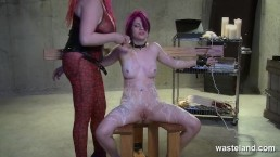 Female submissive is covered in hot wax in the femdom dungeon