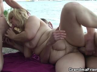 Blonde granma swallows two cocks near lake