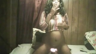black girl smoking and playing with a lava lamp