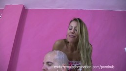 Domme is spitting on slave's bald head covering him with saliva