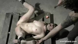 Brunette sex slave chained to pallet on the dungeon floor and caned Cleavage tits