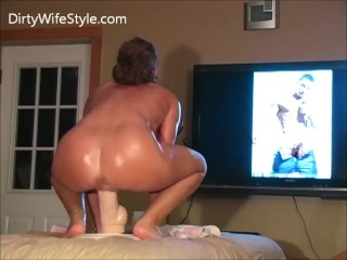 MILF rides monster dildo while looking at pictures of guys with big cocks