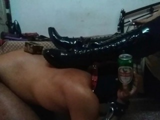 Mistress Makali uses a slave as a foot stool and a bottle holder
