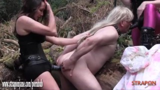 Horny femdoms fuck and spit roast blonde sissy slut in woods with strapons