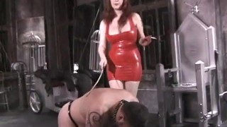 Stunning latex-clad redhead domina has some fun with her man  spanking dominatrix babe bdsm redhead femdom old dungeon sex-toys kink latex whipping nipple-pinching