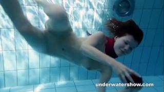 Redhead Mia stripping underwater