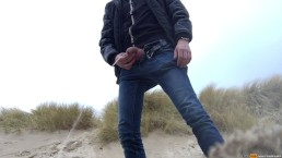 young man urinates in the dunes