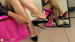 Sexy redhead puts stiletto on her bare feet