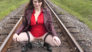 Naked in public. Mature woman without panties poses near train. Piss public