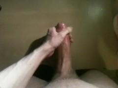Polishing glans of huge uncut cock and shooting huge load across desk