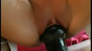 Young brunette beauty fills her pussy with a fat dildo