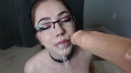 Rubia avec des lunettes suce un gode qui lui éjacule dans la bouche et au visage