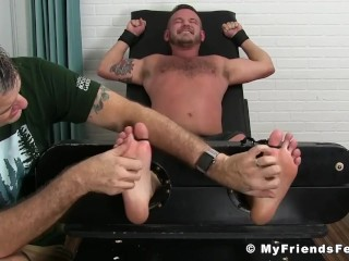 Tattooed jock tied up to a bed while getting his feet tickled hard