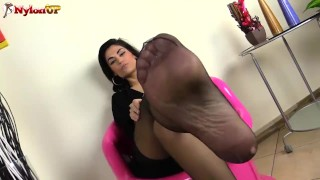 Brunette nude in pantyhose smells her feet