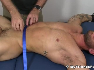 Muscular hunk tied up to a bed while his body is tickled hard