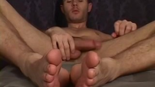 Feet loving jock stroking his long dick until he squirts cum Smelling foot