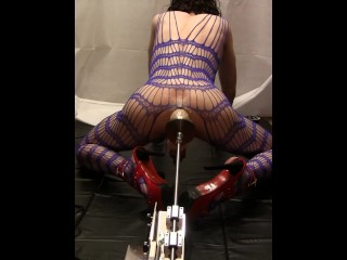 TS with inflatable dildo on a sex machine, behind view