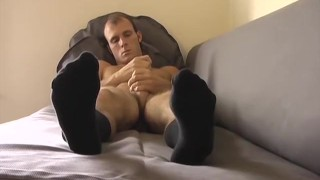 Handsome young stud jacks off with his feet in the forefront