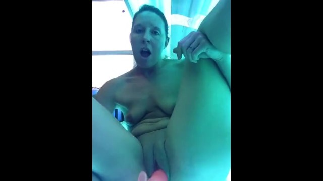 Tanned milf fuck - Wife fucking her pussy with a dildo on her tanning bed