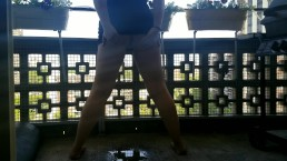 Girl pees standing up on public balcony