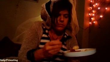 FtM little eating fish sticks in a onesie
