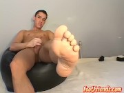Handsome young man masturbates while cockteasing with feet