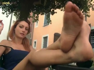Sexy Barefoot redhead gives a foot show outside a bar