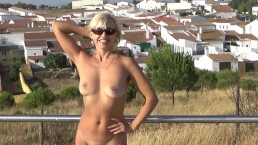 Naked blonde is walking in the Spanish city.