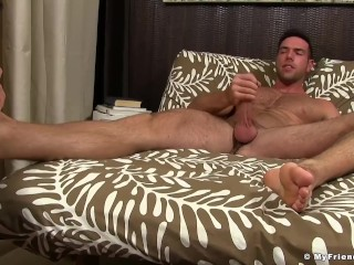 Hunk jerks off while having his feet sniffed and licked