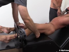 Tattooed hunk on the bondage device tickled by two fellas