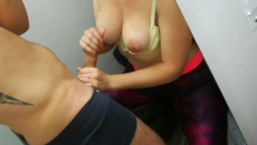 Messy handjob in store's fitting room: cum on her big tits