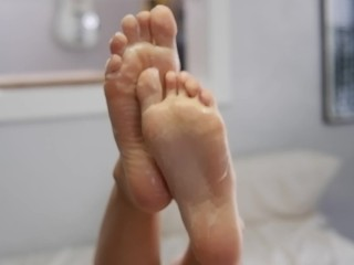 Wrinkled soles with cute toes covered in lotion