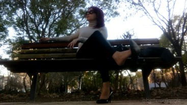 I am dangling my black pumps and my leather pants on a bench in the park