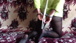 покорная юная девушка в наручниках и колготках с нейлоновым воротником показывает себя