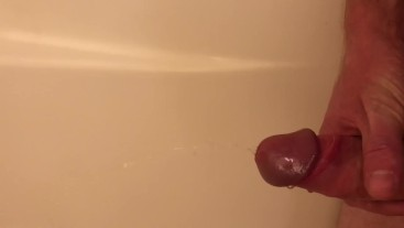 Guy pisses in the tub, then jerks himself off until he cums