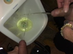 Boys piss and spit together at the urinal after some cocktails