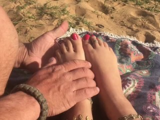 Hippie girl gets foot massage at a public beach