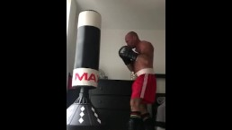 working the bag in red boxing trunks