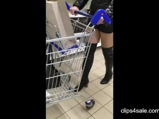 In the supermarket . Mom in shiny jacket, leather shorts and overknee boots