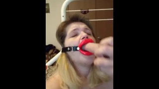 Trying to talk while giving a blowjob to Dildo, wearing open mouth gag