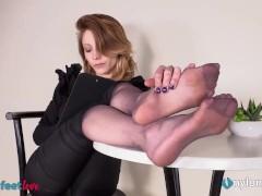 La capo ufficio gioca con le scarpe e mostra i piedi in nylon