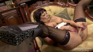A milf wife masturbates with a dildo in her living room