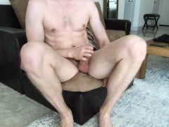 Guy spreads his muscular legs, jerks off his white dick and cums