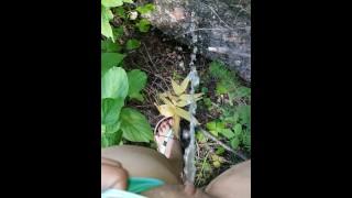 Girl In Swim Suit Pees On Fallen Tree By River