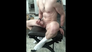 Muscular guy in Nike white sock plays with uncut cock