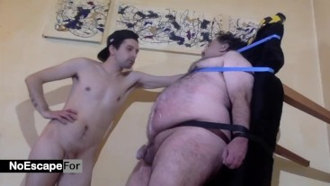 young master immobilizes his mature slave to torture him